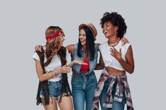 Three attractive stylish young women. Looking at each other and laughing while standing against grey background stock photos