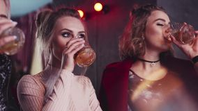 Three attractive women having a friendly conversation with cocktail glasses and drink a toast. Happy together, modern stock footage