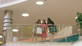 Three attractive women meeting in shopping mall and showing their purchases. To each other stock video