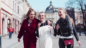 Three attractive women walking in the city center of an old city, laughing and sharing stories. Stylish outfit and. Makeup. Sunny weather. Old city architecture stock video