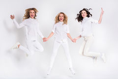 Three attractive women in white jumping on white background Royalty Free Stock Photo