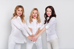 Three attractive women in white portrait on white background. Three attractive women with united hands in white clothing on white studio background. Blonde Stock Photo