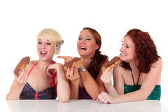 Three attractive young enjoying the temptation. Three attractive young women enjoying the sweet temptation. Women ready to eat the éclairs. Studio shot. White Royalty Free Stock Photos