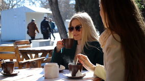 Three attractive young girls sit at an outdoor cafe and talk. Three attractive young girls at a Cafe and talk stock video footage
