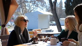 Three attractive young girls sit at an outdoor cafe and talk. Three attractive young girls at a Cafe and talk stock footage