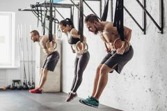 Three young male and female adults doing pull ups on rings. Three attractive young male and female adults doing pull ups on rings royalty free stock photography