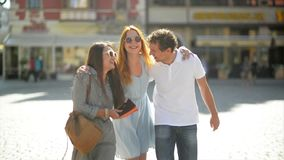 Three Attractive Young People Met in the Street and They are Happy To Spend Time Together. Two Girls in Sunglasses and. Short Dresses and One Boy in White Shirt stock footage