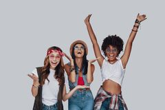Three attractive young women. Cheering and smiling while standing against grey background stock image