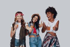 Three attractive young women. Keeping thumbs up and smiling while standing against grey background royalty free stock photography