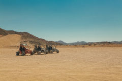 Three atv standing in hot desert Stock Photos