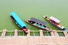 Three auto boats landing at bamboo pier Stock Photography