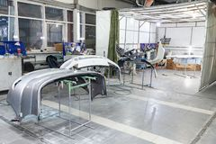 Three auto bumpers  parts are installed on the racks after painting in the car repair shop in the room with tools and equipment royalty free stock photography