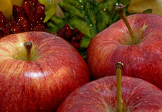 Three Autumn Apples With Fall Leaf Background. Three red stemmed apples with a fall foliage bur background Royalty Free Stock Image