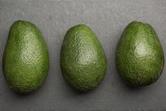 Three avocado top view on a dark background . royalty free stock photography
