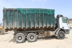 Three axle hook lift truck. Hook lift truck for waste transport returns back to the waste transfer station after having unloaded in a sanitary landfill stock photo