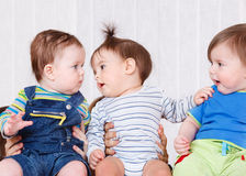 Three babies. Sit together communicating Royalty Free Stock Images