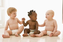 Three babies sitting indoors holding hands. Three babies sitting on the floor indoors holding hands stock photos