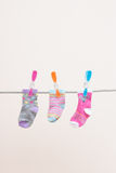 Three Babies Socks On Washing Line. A photograph of three babies socks on a washing line. Hung out to dry with colorful clothespins Royalty Free Stock Photo
