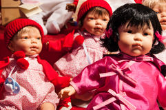 Three baby dolls in colorful clothes. Royalty Free Stock Photos