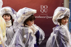 Three baby majorettes wrapped up against rain at Carnival parade Stock Image