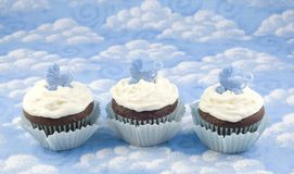 Three Baby Shower Cupcakes for Boy. Three chocolate cupcakes with vanilla frosting for a baby shower for a boy, blue sky background with clouds, selective focus royalty free stock image