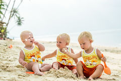 Three baby Toddler sitting on a tropical beach in Thailand and playing with sand toys. The yellow shirts. Two boys and one girl Stock Photos