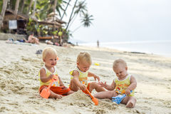 Three baby Toddler sitting on a tropical beach in Thailand and playing with sand toys. The yellow shirts. Two boys and one girl Stock Photo
