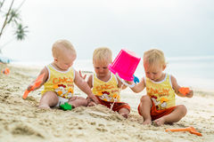 Three baby Toddler sitting on a tropical beach in Thailand and playing with sand toys. The yellow shirts. Two boys and one girl Stock Image