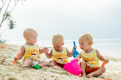 Three baby Toddler sitting on a tropical beach in Thailand and playing with sand toys. The yellow shirts. Two boys and one girl Royalty Free Stock Images
