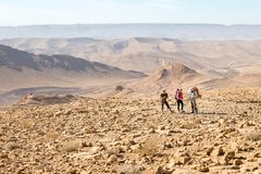 Three backpackers standing mountains trail , Negev desert, Isra royalty free stock photography