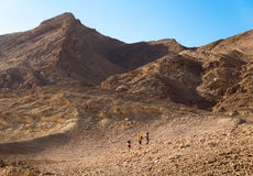 Three backpackers walking ascending mountain stone desert trail. Royalty Free Stock Photo