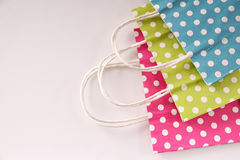 Three bags colored with circles on a table top view. Three paper bags to buy colored with white circles stacked in a row on white table. Top view Stock Image