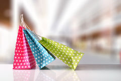 Three bags colored with white circles in a mall front. Three paper bags to buy colored with white circles on reflective white table in a shopping center. Front Royalty Free Stock Photo