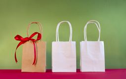 Three bags decorated with bow on red and breen bac Stock Photos