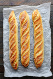 Three baguette on white paper Stock Photos