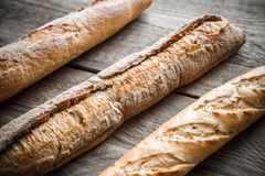 Three baguettes on the wooden background Royalty Free Stock Image