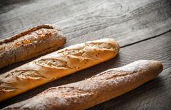 Three baguettes on the wooden background Royalty Free Stock Photography