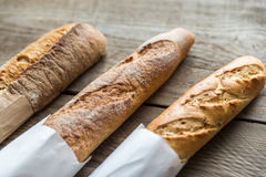 Three baguettes on the wooden background Stock Photos