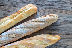 Three baguettes on the wooden background Royalty Free Stock Photos