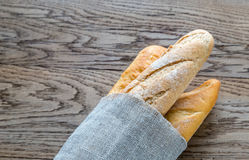 Three baguettes on the wooden background Stock Images