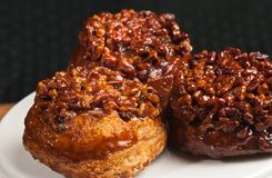 Three pecan sticky buns. Three baked with carmel and whole pecan sticky buns on a pedestal white, round plate Stock Photography