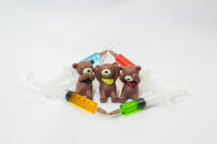 Three baked clay teddy bears with plastic syringes containing multicolor solutions Stock Photography