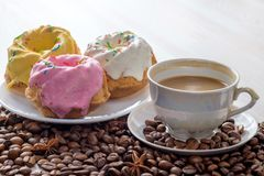 Three baked cupcakes with icing. Three baked cupcakes with icing and cup of coffee with milk on light table. Near it scattered coffee beans. Close-up view Royalty Free Stock Images