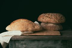 Three baked loaves of bread on a wooden table. Product with pumpkin and sunflower seeds royalty free stock photography