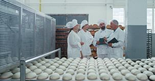 Three bakers with a stylish white uniform and old man engineer in a bakery industry explaining the security notes about. Industrial machine. 4k stock video footage