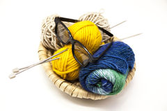 Three ball of woolen threads, yellow, blue, beige and steel knitting needles and glasses in a wooden basket on a white background. Royalty Free Stock Image