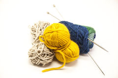 Three ball of woolen threads, yellow, blue, beige and steel knitting needles  on a white background Stock Image