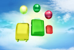 Three balloons and bags on blue sky. Stock Image