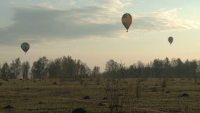 Three balloons hovering over a field stock video footage