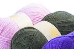 Three balls of coloured wool. In pink, charcoal and purple for knitting a garment, close up view over white Stock Photos